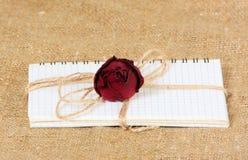Notepaden på metallcirklarna binds med en skopa En torra burgundy steg lögner på en anteckningsbok för tillträden med ark i en bu Arkivfoto
