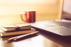 Notepads och pennor med koppen kaffe och bärbara datorn arkivbild