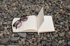 Notepads plans and sunglasses on a gravel road to Royalty Free Stock Photos