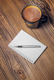 Notepaper, coffee cup and pen on wood table Stock Images