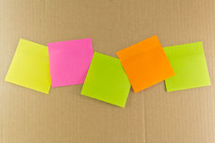 Notepaper postit. Some color adhesive-message on a dark background Royalty Free Stock Photo