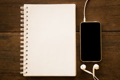 Notepaper and smart phone on wooden table Stock Photos