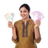 Noterar hållande valuta för den unga indiska kvinnan vit agianst Arkivbild