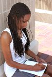 Notes 2. Female student taking notes at a college campus Royalty Free Stock Image