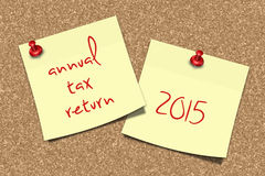 Notes with annual tax return text pinned to pin board Royalty Free Stock Photos