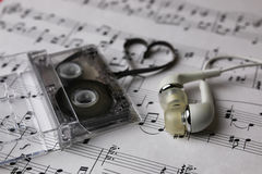 Notes background and headphones. Audiocassette retro music and film of her folded in the shape of a heart and headphones Royalty Free Stock Photo