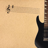 Notes and black electric rock guitar on the right side of rough cardboard background. Royalty Free Stock Image
