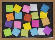 Notes blanc colorées sur le tableau noir Photos stock