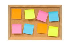 Notes on a bulletin board. Multicolored - flourescent colored post it or sticky notes on a bulletin - cork board.  with clipping path Royalty Free Stock Photo