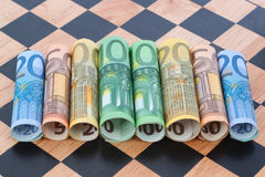 Notes on a chessboard. Money on a wooden chessboard Stock Photography