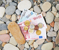 Notes and coins on sea pebble Stock Photo