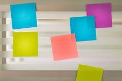 Notes collantes colorées dispersées au-dessus de l'écran en verre d'un bureau de banc Photo libre de droits