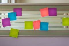Notes collantes colorées dispersées au-dessus de l'écran en verre d'un bureau de banc Image stock