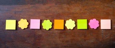 Notes colorées collantes dans des formes de fleur et de place, d'isolement, bannière, l'espace de copie sur le fond en bois photographie stock libre de droits