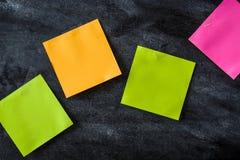 Notes colorées de bâton sur le fond de tableau noir Photographie stock