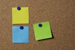 Notes on a cork board. 3 blank coloured notes, pinned onto a cork board Stock Photos