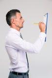 Notes d'écriture d'homme d'affaires dans le presse-papiers Images stock
