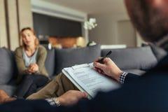 Notes d'écriture de psychologue pendant une session de thérapie avec le patient photos libres de droits