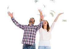 Notes de lancement de devise de jeunes couples heureux en air Images stock