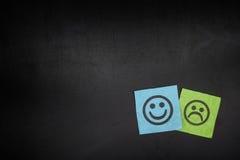 Notes de Livre vert bleu et avec les visages heureux et tristes sur blackboar Photo stock