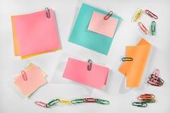 Notes de papier colorées vides multiples et trombones colorés sur le fond blanc. image stock
