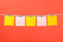 Notes de papier jaunes et roses vides sur la ficelle Photographie stock