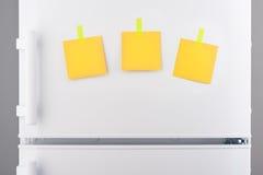 Notes de papier jaunes jointes en annexe avec des autocollants sur le réfrigérateur blanc Photographie stock