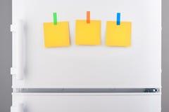 Notes de papier jaunes jointes en annexe avec des autocollants sur le réfrigérateur blanc Images stock