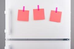 Notes de papier roses jointes en annexe avec des autocollants sur le réfrigérateur blanc Photographie stock