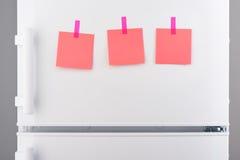 Notes de papier roses jointes en annexe avec des autocollants sur le réfrigérateur blanc Photos libres de droits