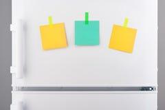 Notes de papier vertes et jaunes vides jointes en annexe sur le réfrigérateur Photographie stock