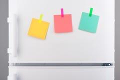 Notes de papier vertes, roses et jaunes jointes en annexe sur le réfrigérateur Photo stock