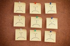 Notes de post-it avec les visages tristes sur des babillards photo stock