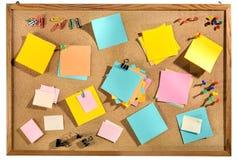 Notes de post-it et fournitures de bureau colorées vides sur la table des messages de liège. Photographie stock libre de droits