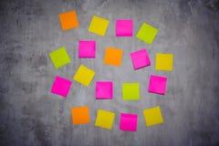 Notes de post-it lumineuses sur le mur gris Image libre de droits