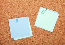 Notes de post-it vides sur le panneau d'affichage de liège Image stock