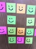 Notes de sourire colorées avec la porte en bois de fond image stock
