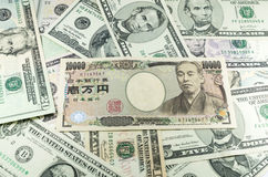 Notes de Yens japonais sur le fond de beaucoup de dollars Photographie stock