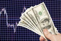 Notes du dollar à disposition sur un fond bleu avec le programme Photographie stock
