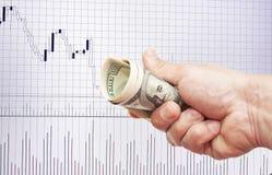 Notes du dollar dans une main sur un fond blanc du programme Photo stock