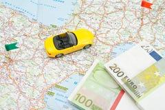 Notes et voiture jaune sur la carte Image stock