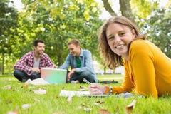 Notes femelles d'écriture avec des étudiants à l'aide de l'ordinateur portable au parc Photos libres de droits