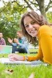 Notes femelles d'écriture avec des étudiants à l'aide de l'ordinateur portable dans le parc Image libre de droits