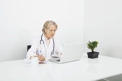 Notes femelles supérieures d'écriture de docteur tout en regardant l'ordinateur portable dans la clinique Photo libre de droits