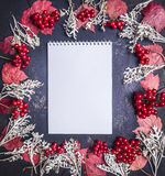Notes with frame of autumn leaves, berries and decorations on wooden rustic background top view close up space for text Royalty Free Stock Photos