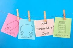 Notes hang on clothes pegs with drawings of children's inventions - popsikl, Earmuffs, calculator on a blue background. Text - Ki. D Inventors' Day Stock Photography