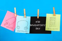 Notes hang on clothes pegs with drawings of children's inventions - popsikl, Earmuffs, calculator on a blue background. Text - Ki. D Inventors' Day Royalty Free Stock Image