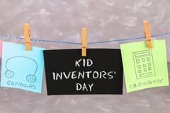 Notes hang on clothes pegs with drawings of children's inventions - popsikl, Earmuffs, calculator on a gray background. Text - Ki. D Inventors' Day Royalty Free Stock Photos