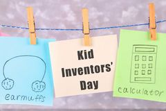 Notes hang on clothes pegs with drawings of children's inventions - popsikl, Earmuffs, calculator on a gray background. Text - Ki. D Inventors' Day Royalty Free Stock Images