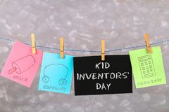 Notes hang on clothes pegs with drawings of children's inventions - popsikl, Earmuffs, calculator on a gray background. Text - Ki. D Inventors' Day Stock Image